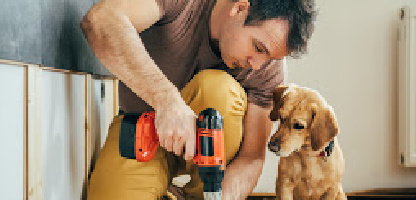 Man with dog using a screwdriver