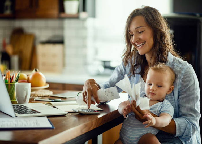 Mom and baby sitting at table with computer