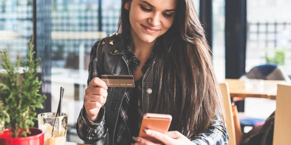Girl holding credit card and cell phone