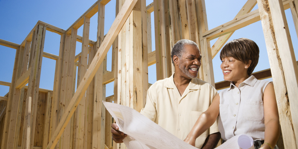 Couple with blue prints outside building home addition