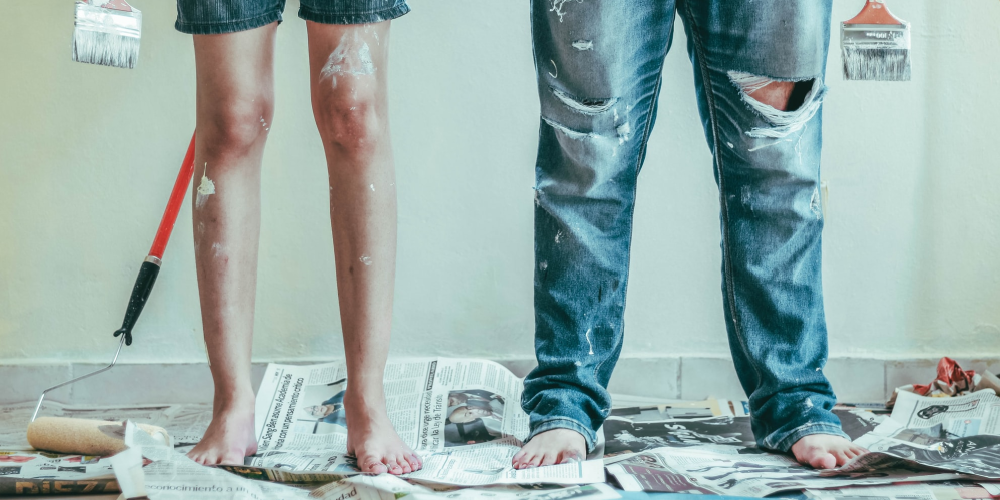 Man and woman standing with paint rollers on newspaper