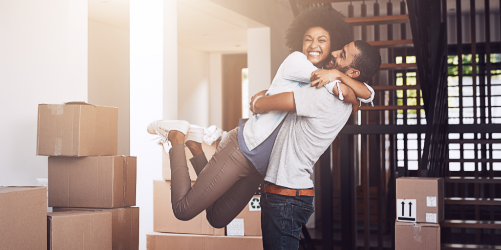 Couple hugging in new home with boxes around them