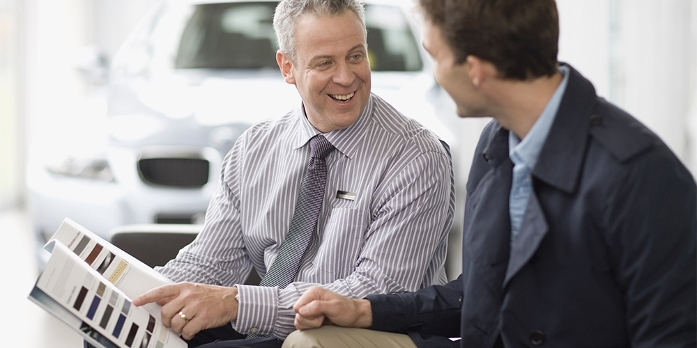Men discussing car options at dealership