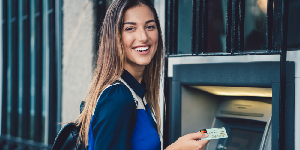 Young girl at ATM machine with Debit Card
