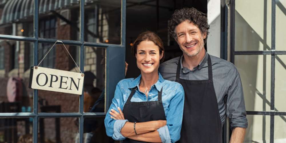 Business owners in front of open sign on door