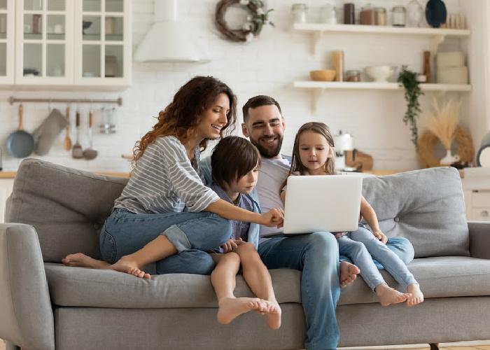 Family of four on couch looking at laptop